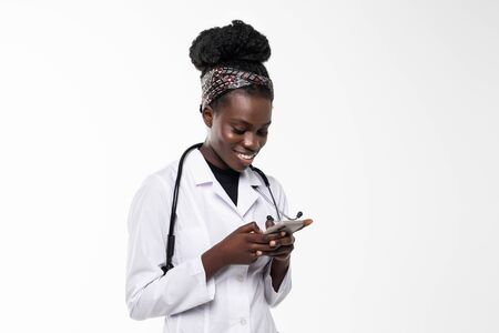 Smiling female doctor holding a mobile phone in the hospital