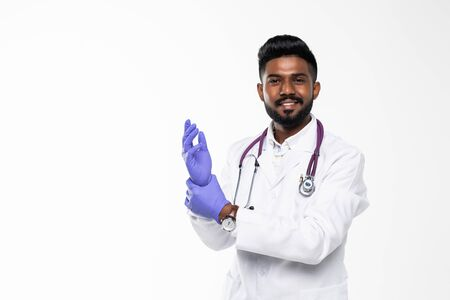 Indian doctor or physician male looking at hand with focused expression as putting on blue surgical latex glove isolated on white