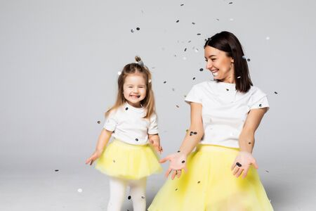 Young mother and small daughter playing with confetti isolated on white background