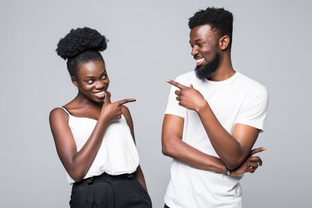 Blaming each other. Beautiful young African couple pointing each other while standing isolated on white background Stock Photo - 130034348