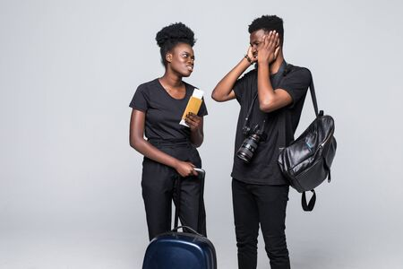 Full length portrait of young african couple walking with suitcases for travel isolated over white background