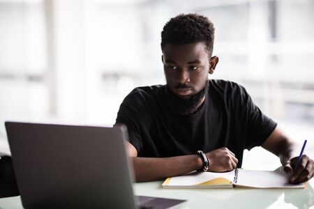 Image of young African man looking at camera with laptop near by 免版税图像 - 130038559