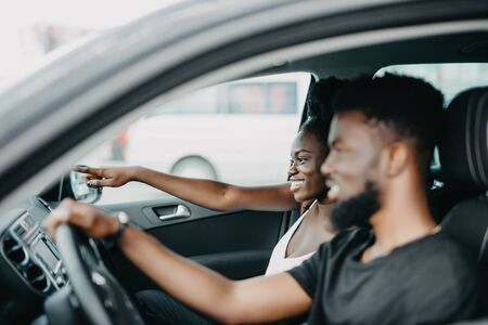 african woman pointed with hands while african man drive car on the road 写真素材 - 130034690