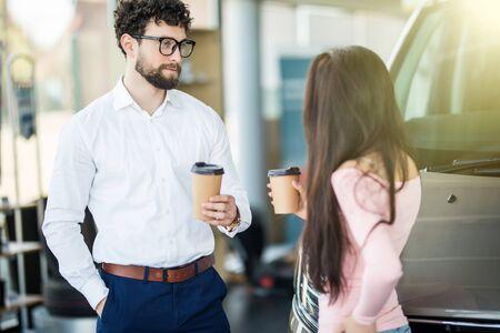 Salesperson showing vehicle to potential customer in dealership Banco de Imagens