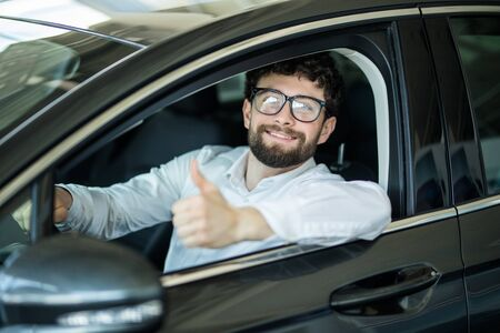 Happy handsome man smiling cheerfully showing thumbs up sitting in a new auto at the dealership salon 版權商用圖片