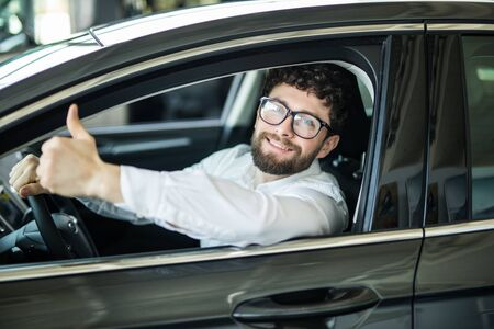 Dream came true. Cheerful casual guy smiling happily showing thumbs up sitting in a big white car