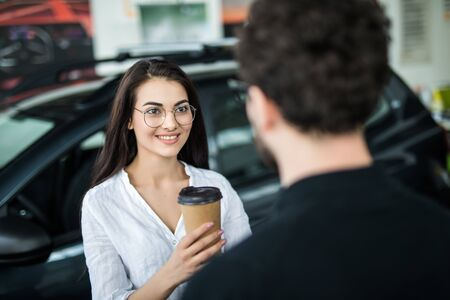 Beautiful girl is drinking coffee in the new car. She is in dealership looking for new car. Car is red. She is smiling. Banco de Imagens