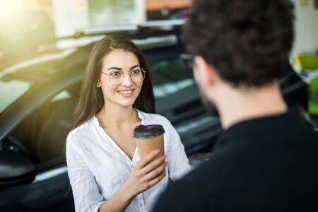 They are very happy about this, they are in a good mood. There are many modern cars. Banco de Imagens