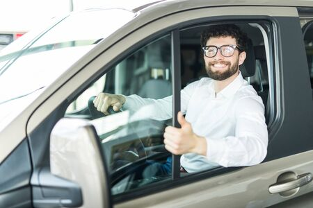 Thumbs up. Portrait of a happy man showing thumbs up sitting in his new car 写真素材