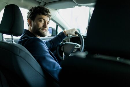 Rückansicht des Mannes, der im neuen Auto im Ausstellungsraum sitzt.