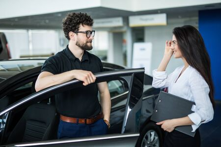 Manager showing something on a clipboard to the customer in car showroom