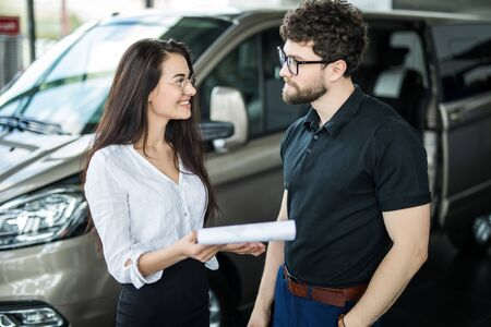 Sales manager showing to happy customer a car he won