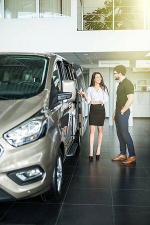 Young female car sales consultant working in showroom