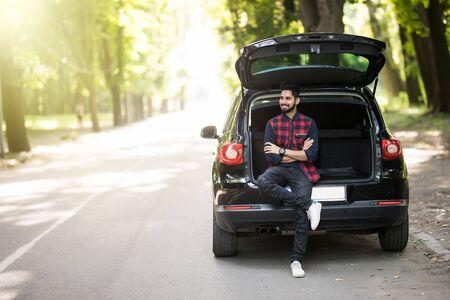道路上の彼女の車のトランクに座っている若い男 写真素材