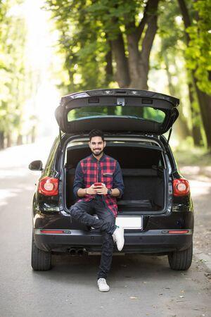 若いインド人男性は、道路上のトランクに座って彼女の携帯電話を使用しています。