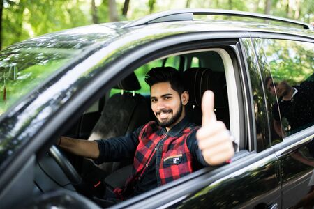 Attractive young man sitting in his car with thumb up smiling at the camera Reklamní fotografie