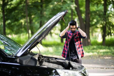 Closeup portrait, young man having trouble with his broken auto, opening hood trying to fix engine, isolated green trees outside background. Car won't start, dead battery Stock fotó
