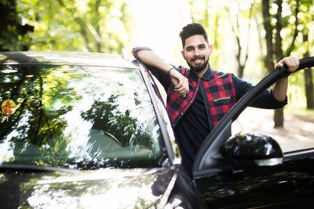 站立在路的英俊的人在他的汽车的被打开的门。