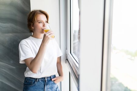 Young woman morning at home near window drinking juice, vitamin drink