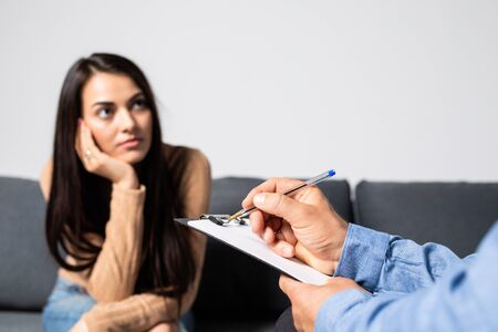 Young lady having depression sitting on the couch opposite to psychotherapist and crying.