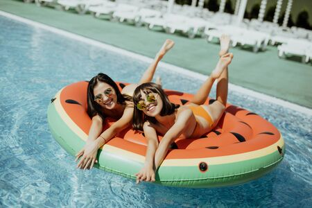 Portrait of female friends lying on an inflatable toy sunbathing on floating pool.