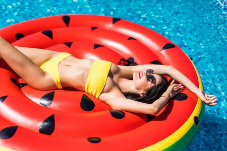 Young sexy pretty woman relaxing in a swimming pool leisure on a big fashion watermelon donut float topless