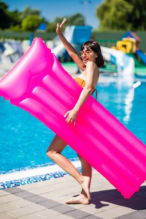 beautiful young woman with inflatable mattresses standing at poolside and looking at camera