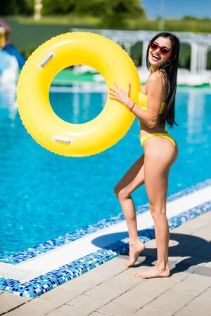 Beautiful woman in bikini holding a inflatable ring at poolside and smiling. Female wearing bikini and sunglasses enjoying her holiday at resort poolside.