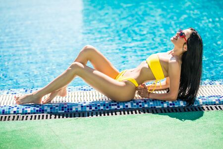 Beautiful bright sexy funny woman lies on the edge of the pool, sunbathing, enjoys. Stock Photo
