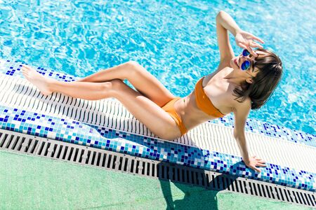 Beautiful women relaxing at the luxury poolside. Girl at travel spa resort pool.