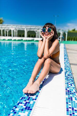 Beautiful young girl sitting near swimming pool Stock Photo