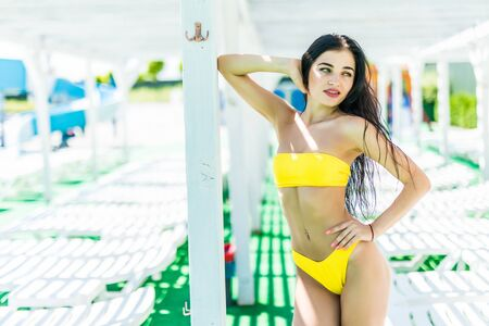 Cherful young sexy woman in resort, holiday, vacation, standing, posing next to the pool. Wearing fashionable glasses, black bikini, sunglasses.