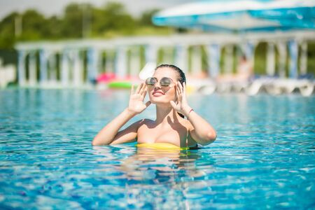 Beautiful women relaxing at the luxury poolside. Girl at travel spa resort pool. Summer luxury vacation.