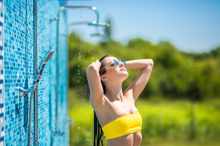 Beautiful young woman taking relaxing shower while standing near swimming pool outdoors