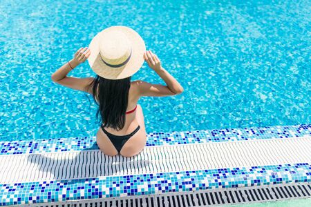 Bikini woman in pool relaxing rear view, resting in vacation on summer season with hat at resort swimming pool edge