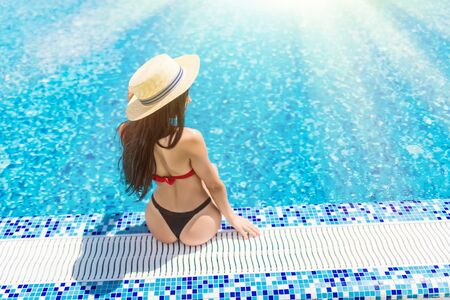 Rear view of sexy woman in bikini sitting on the edge of pool. Summer vocation.