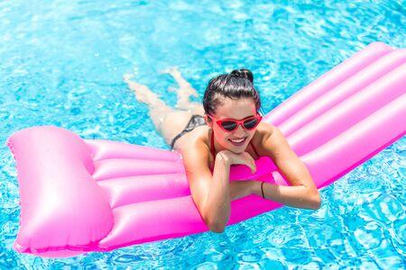 Mujer joven en gafas de sol y bikini acostado sobre un colchón inflable flotando en la piscina Foto de archivo