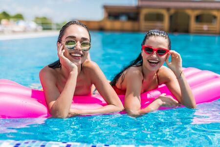 Dos niñas están nadando en una piscina sobre colchones inflables.