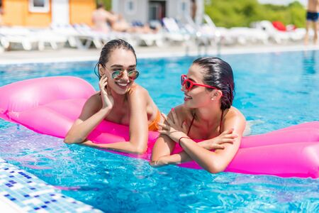 Two girls are swimming in a pool on inflatable mattresses Stock Photo