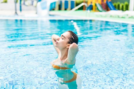 Woman at the Edge of a Swimming Pool Stock Photo