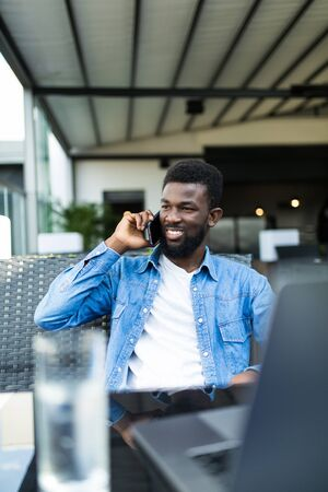 Handsome black man talking on smart phone, looking aside and smiling. He is at cafe bar. Stock Photo
