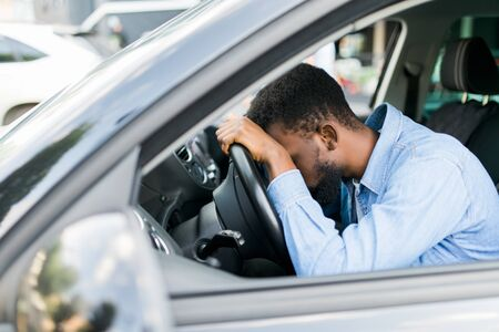 Overworked personal driver falling asleep on steering wheel of car, tired man
