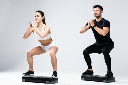 Athletic couple doing exercises over steps in aerobic class on a fitness center.