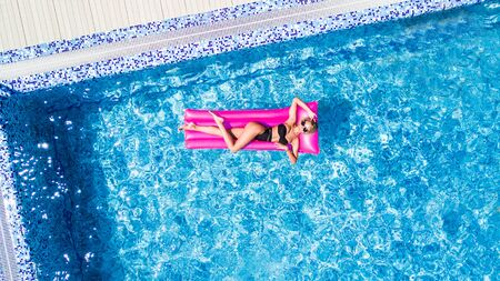 Beautiful Young Woman sunbathing on inflatable pink mattress at swimming pool
