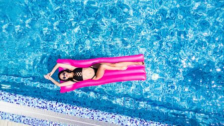 Slim young woman lying on air mattress in the pool Stockfoto