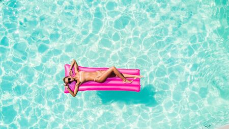 Attractive woman in bikini relaxes in the pool with a floating mattress Stock fotó