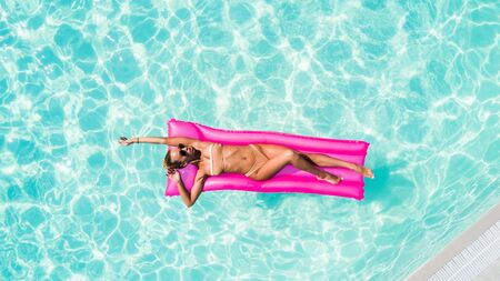 Sexy woman takes a sunbath on a float in the pool, aerial shot Stock Photo