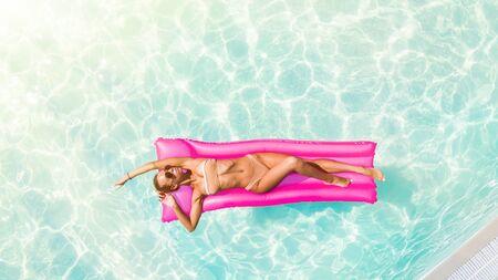 Enjoying suntan Woman in bikini on the inflatable mattress in the swimming pool.