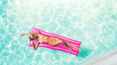 Sexy woman sunbath on a float in the pool, top view aerial shot. Young woman in a bikini swimsuit floating on an inflatable pink mattress top view