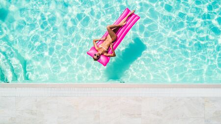 Sexy woman takes a sunbath on a float in the pool, aerial shot Stock fotó
